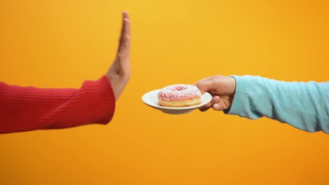 Hand showing stop sign rejecting glazed donut on bright background, weightloss
