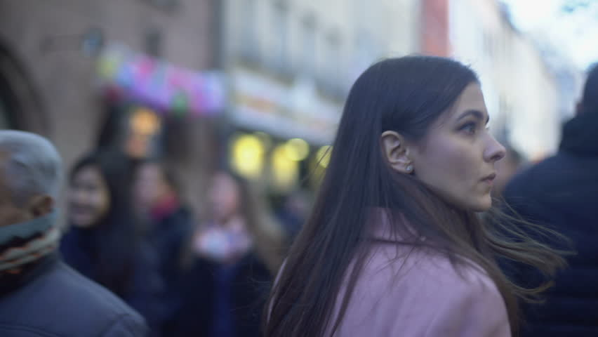 Nervous young female criminal walking on crowded street and turning around | Shutterstock HD Video #1025609165