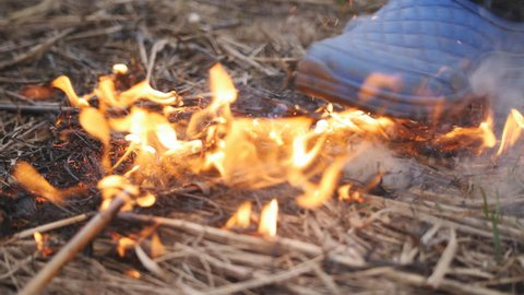 The woman in galoshes extinguishes the flaring dry grass stepping on a fire.