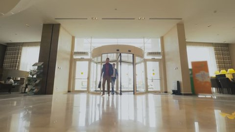 Business men coming into revolving doors in modern business center. Business people entering in lobby and walking on hallway in luxury hotel. France, Paris - November, 2018.