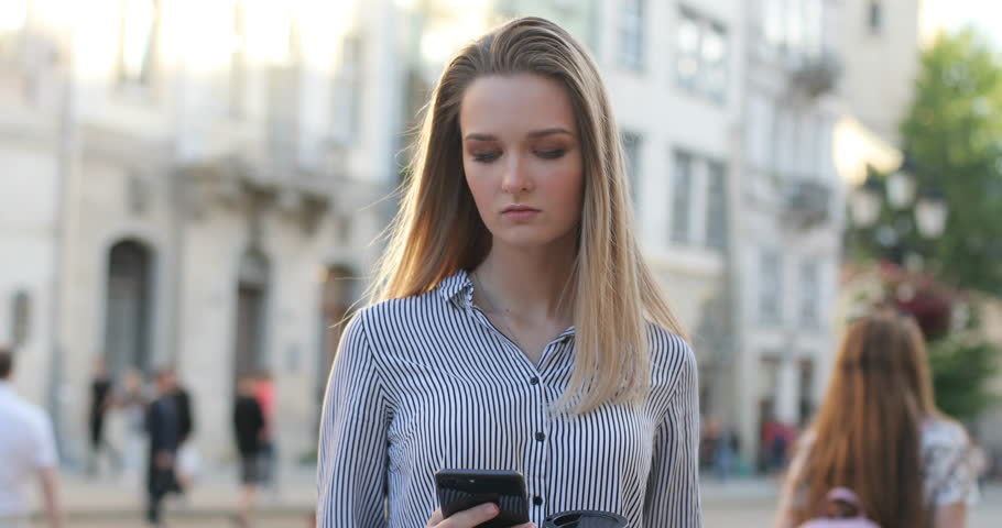 Close-up round view of a young caucasian blonde woman in a shirt using her mobile phone on a street, slow motion.