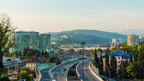 Time-lapse video of day to night transition. Aerial view of city, mountains and Doubler of Kurortnyy Prospekt highway, Sochi, Russia