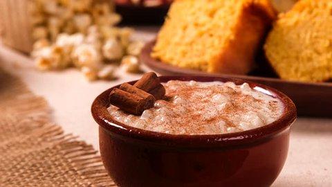 Brazilian dessert canjica of white corn with cinnamon in bowl. Selective focus. Table of brazilian festa junina with smoke.