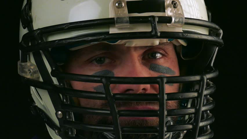 American football. Close-up of american football player in helmet looking into camera. Confident look of an American football player. Black background