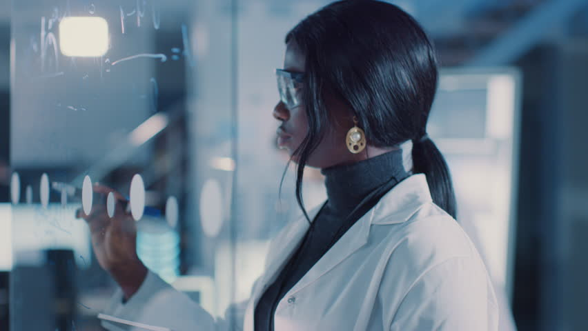In the Research Laboratory Smart and Beautiful African American Female Scientist Wearing White Coat and Protective Glasses Writes Formula on Glass Whiteboard, References Her Tablet Computer | Shutterstock HD Video #1025738195