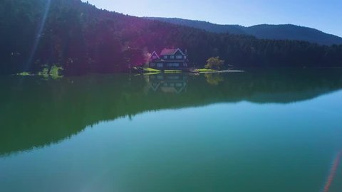 aerial drone ascending shot, flying towards mansion aside Abant Lake, revealing forest, lake reflecting scenic forest, in Bolu, Turkey