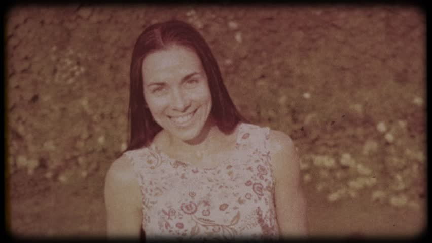 Family video archive. Retro camera 8 mm. Old film. Young attractive woman having fun in the green garden. Portrait of a smiling brunette with dimpled cheeks against a green park. Pretty girl in summer
