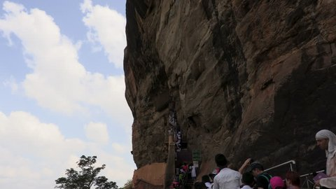 SIGIRIYA, SRI LANKA - MARCH 2019: People climbing to the top of the Rock Fortress in Sigiriya, an ancient palace located in the central Matale District.