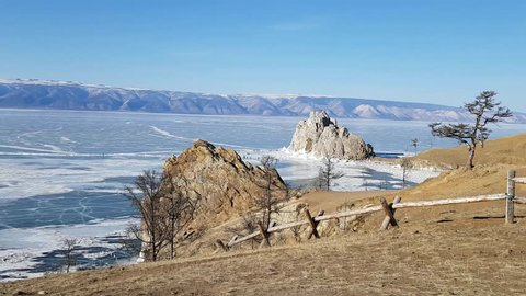 Panoramic view of Shaman rock and Cape Burhan on Olkhon island in Russia. Lake Baikal in ice. Winter trip to Russia. The camera shows a panoramic view of the lake and the opposite shore