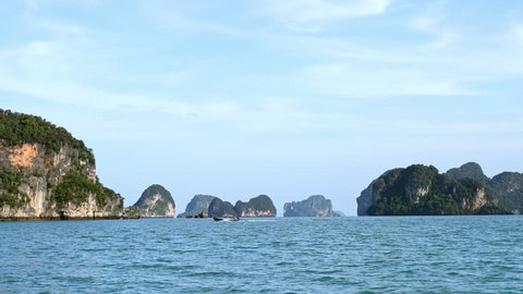 Cliff islands of Phang Nga bay in Thailand sea. Traditional thai boat travels fast