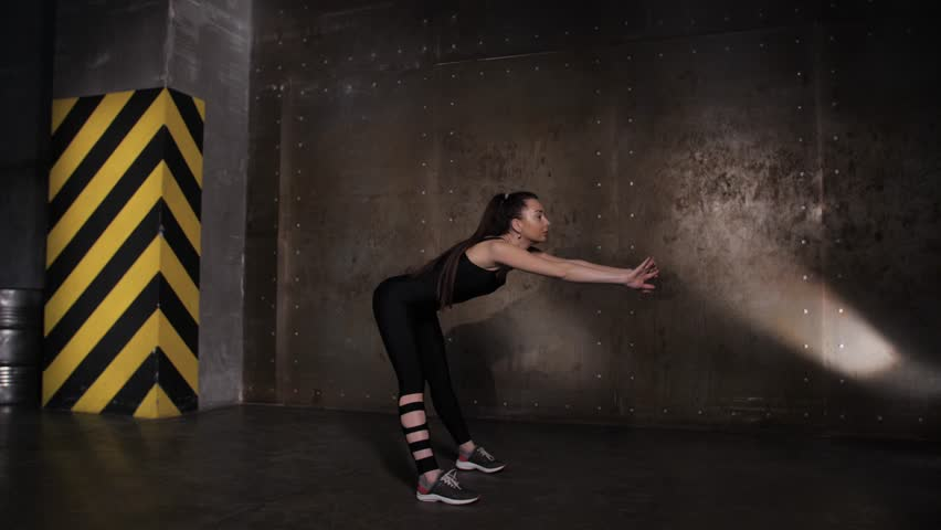 Athlete performs exercises from the group program with dumbbells. Dark loft hall | Shutterstock HD Video #1025792645