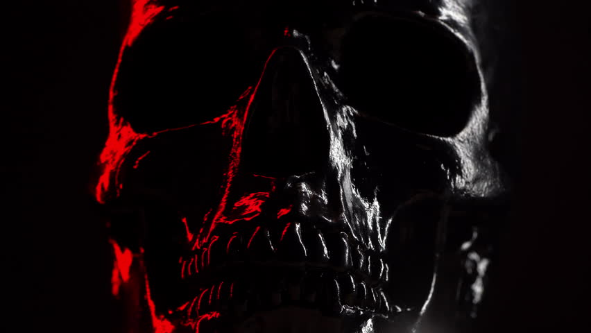 Model of human skull painted with black on dark background with variable red illumination. Spooky and sinister., Halloween celebration | Shutterstock HD Video #1025811725