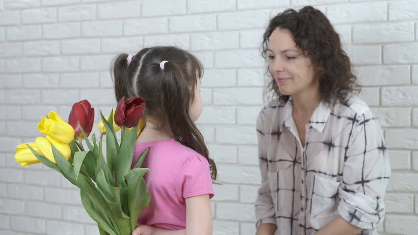 Mothers Day. The child gives flowers to the mother. | Shutterstock HD Video #1025828135