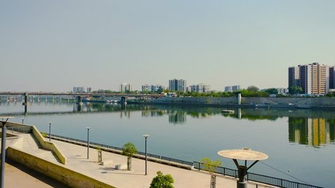 Ahmedabad, Gujarat, India - Circa 2018: Panning shot of the river front of Ahmedabad from the sabarmati ashram in Gujarat . Shows the walkway by the riverside, the skyscrapers in the distance and the
