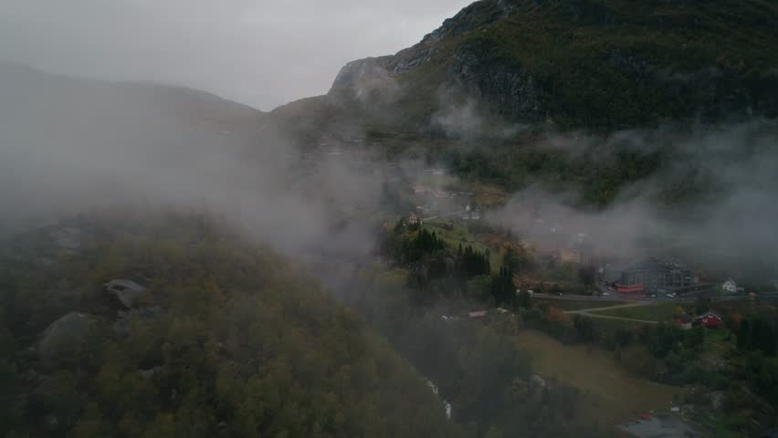 Aerial view. Foggy landscape in Norway. Village in wild nature. RV on the road. Drone footage. | Shutterstock HD Video #1025904635