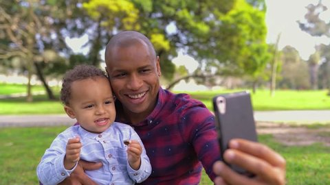 Afro-american young bald father in striped shirt and jeans sitting on haunches in park, holding his little mixed-race son on knees, making selfie. Front view. Family, holiday concept