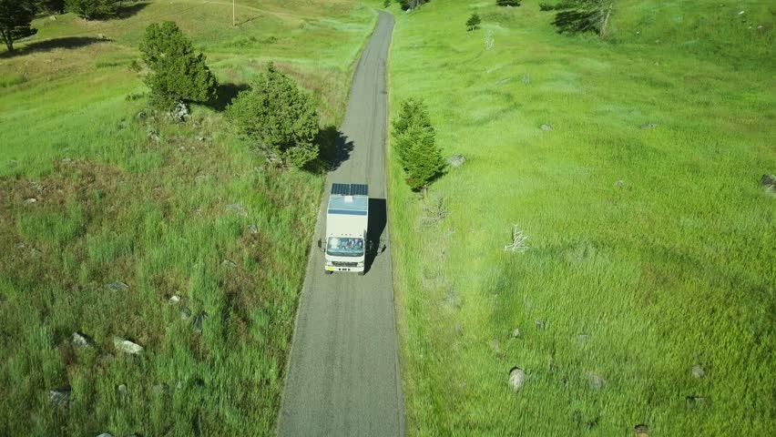Expedition vehicle driving through beautiful green grass lands. Travelling, exploring and adventure concept. | Shutterstock HD Video #1025939225