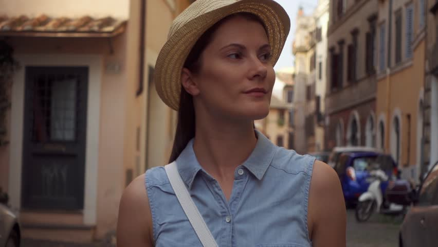 Young woman in hat walking down small old street in Rome, Italy. Happy female traveler in Trastevere district. Slow motion of girl looking around outside in european city | Shutterstock HD Video #1025940035