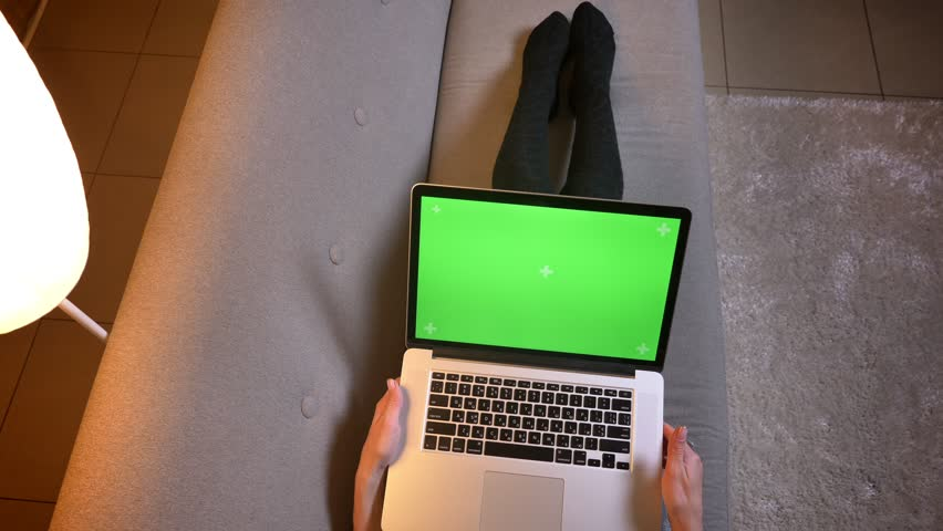 Closeup shoot of young female blogger using social media while typing on the laptop with green screen. Girls legs in cute socks on the cozy sofa | Shutterstock HD Video #1025959535