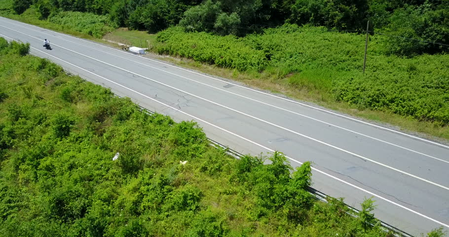 Drone camera following a biker in a highway | Shutterstock HD Video #1025963975