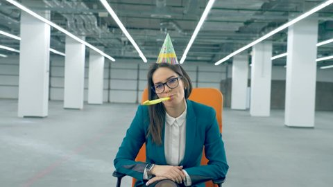 One office worker in a birthday cap blows a whistle, sitting in a chair.