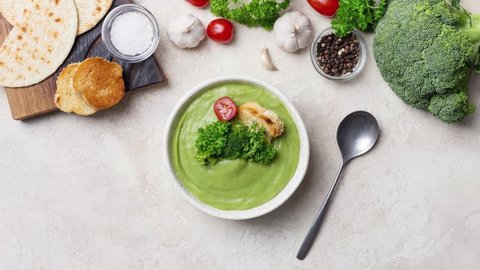 Ingredients for broccoli cream soup with parsley and crouton. Stop-motion of broccoli, parsley, garlic, tomatoes, bread and bowl with broccoli cream soup with spoon at light background