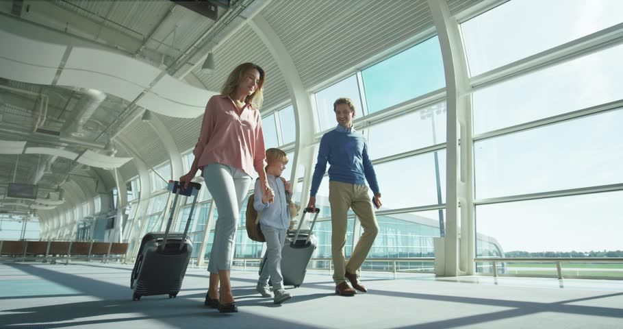 Caucasian parents with small nice son and big suitcases on wheels passing through the camera in the airport passage while going to the departure or arrival gates. | Shutterstock HD Video #1026000335