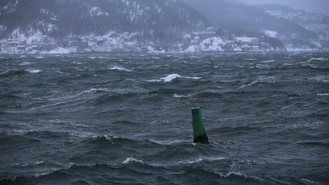 Floating green buoy near the harbor in Trondheim, middle Norway. Wavy water of Trondheimsfjorden fiord. Winter storm.