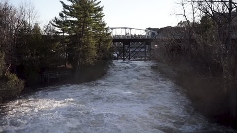 Rushing rapids under the iconic Bracebridge bridge in Muskoka, Ontario Canada