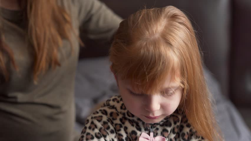 Close-up portrait of a cute red-head girl and her mother who is carefully combing her hair. Both of them are looking pensive and thoughtful. | Shutterstock HD Video #1026042695