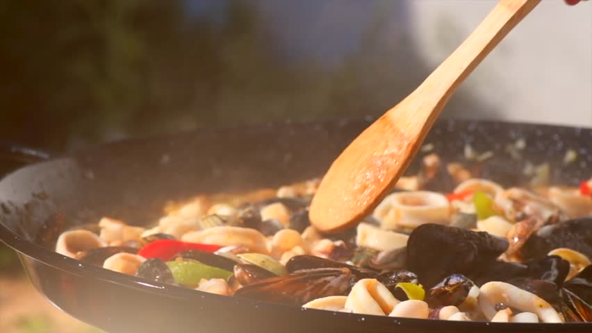 Paella traditional Spanish food, seafood paella in the fry pan with mussels, king prawns, langoustine and squids. Person cooking paella outside. Slow motion 4K UHD video