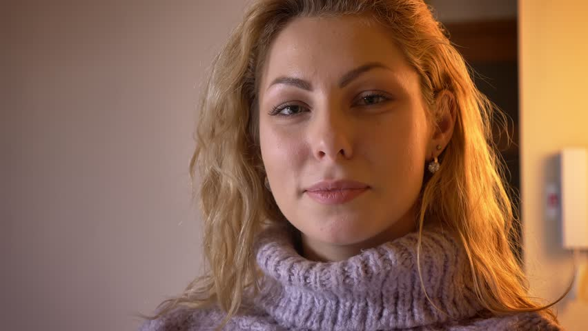 Closeup portrait of adult pretty caucasian blonde female looking at camera and smiling cheerfully in a cozy apartment #1026068585
