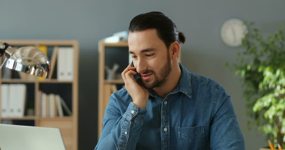 Close up of the caucasian young handsome man sitting in the office and talking on the mobile phone. | Shutterstock HD Video #1026084125