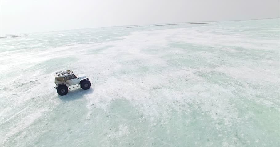 Zooming in aerial view of swamp buggy driving on picturesque blue ice of huge frozen lake Hanka in Russia | Shutterstock HD Video #1026140345