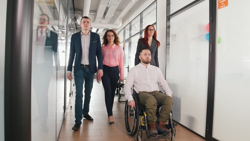 A successful business people walking through the corridor. A man in a wheelchair going first of the group | Shutterstock HD Video #1026190595