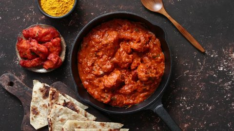 Traditional Indian chicken tikka masala spicy curry meat food in cast iron pan served with naan bread and spices. Flat lay. Top view.