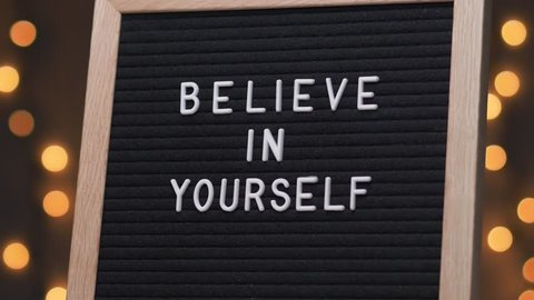Black letter board with BELIEVE IN YOURSELF title on it. Camera rotating around the sign showing the beautiful bokeh balls in the background.