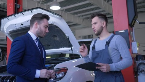 auto repair shop, attractive male client hands over vehicle keys to repairman for professional maintenance and shakes hands near car with open hood at service workshop