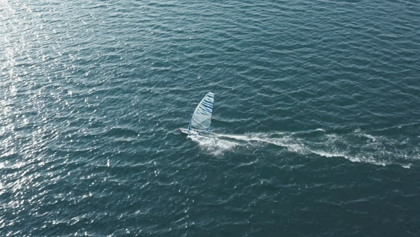 Aerial view of sailing from drone slide upwards on a young windsurfer with board and sail at high speed, coastline and blue sky. Training in windsurfing on small waves. Copyspace | Shutterstock HD Video #1026283265