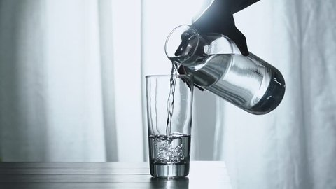 Woman's hand pouring fresh pure water from bottle into a glass on the table, health and diet concept, Slow motion footage