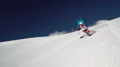 man male skier in race suit with start number one skiing giant slalom training on ski slope on sunny winter day with clear blue sky in slow motion
