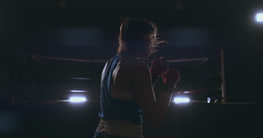 Professional beautiful female boxer otbryvatyvat blows conducting a fight with a shadow in a dark hall of the hall in slow motion in blue clothes and red bandages on her wrists. flying around the | Shutterstock HD Video #1026375425