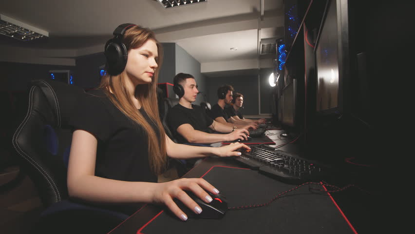 Team of gamers in headphones emotionally rejoices in victory playing in e-sport club, looks at the computer screen and enjoying their triumph. | Shutterstock HD Video #1026382355