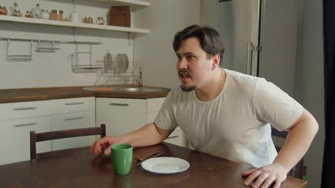 Aggressive jealous husband swearing with wife, blaming for treason and threatening with violence sitting at kitchen table. Ferosious man yelling, getting up from chair, banging on table with anger.