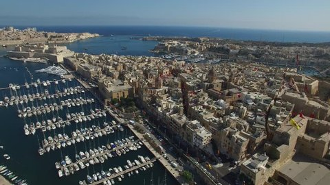 Aerial overview of city streets, marina, and Annunciation Church of Birgu town. Birgu is a neighboring town and a suburb of Valletta, the Capital of Malta.