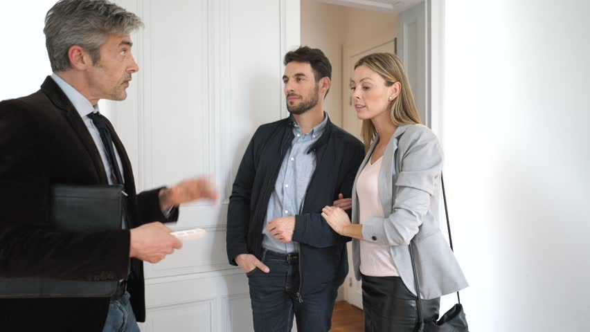 Real estate agent showing couple spacious renovated property | Shutterstock HD Video #1026498605