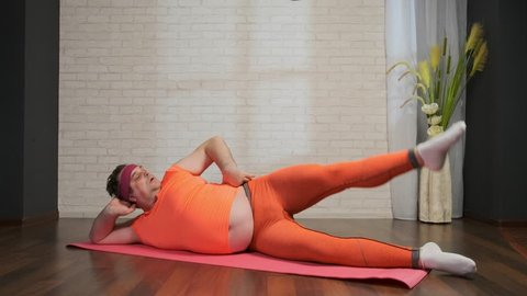 Fat man doing aerobics lying on a gymnastic mat in order to lose weight. Overweight, obesity, exercise.