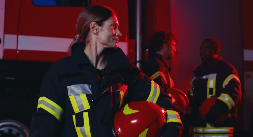 Portrait of the young beautiful Caucasian woman fire fighter with a helmet in hand turning her head to the camera and smiling while standing in front of the big red car and fer male colleagues who