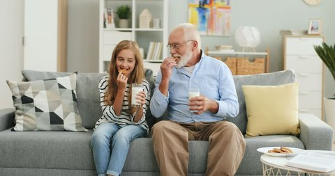 Pretty blonde teen girl sitting together with her grandfather with grey haired on the sofa at home and drinking milk with cookies.