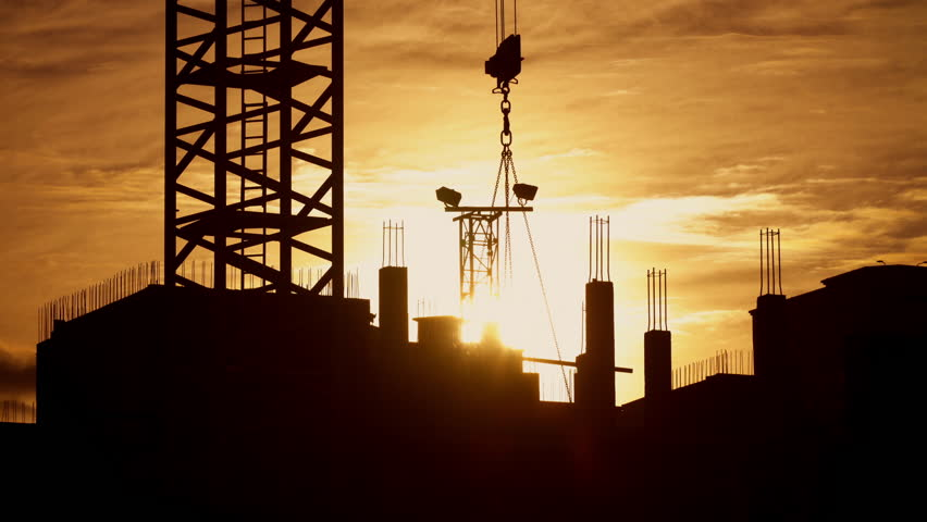 Silhouette of tower crane working on construction site elevate concrete mixer, constructors working on residential building sunny evening, golden hour, warm cloudy sky